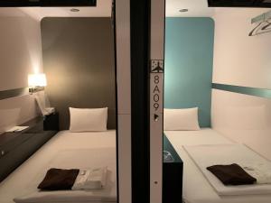 Een bed of bedden in een kamer bij First Cabin Shinbashi Atagoyama