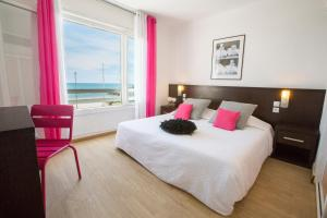 A bed or beds in a room at Le Grand Large Bord de Mer Hotel & Appartements