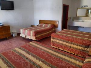 A bed or beds in a room at Hotel Las Palmas