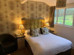 A bed or beds in a room at Skelwith Bridge Hotel