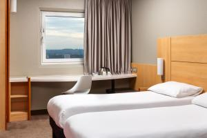 A bed or beds in a room at ibis London Wembley