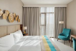 A bed or beds in a room at Holiday Inn Dubai Al-Maktoum Airport, an IHG Hotel