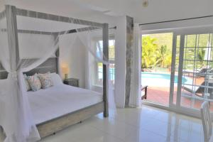 A bed or beds in a room at Marigot Palms Luxury Caribbean Apartment Suites
