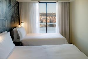 A bed or beds in a room at Expo Hotel Barcelona