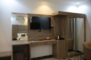 Uma TV ou centro de entretenimento em Beauty Rose Hotel