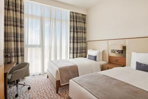 A bed or beds in a room at Staybridge Suites Dubai Al-Maktoum Airport, an IHG Hotel
