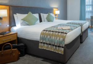 A bed or beds in a room at Westgrove Hotel