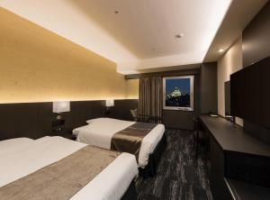 A bed or beds in a room at KKR Hotel Osaka