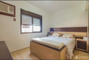 A bed or beds in a room at Apartamento Aconchegante em excelente localização