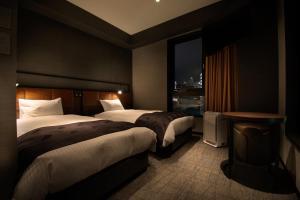 A bed or beds in a room at Joytel Hotel Shinsekai Sakaisujidori