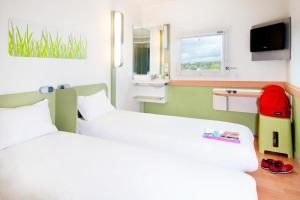 A bed or beds in a room at ibis budget Marseille Aeroport Provence