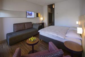 A bed or beds in a room at Parkhotel Brenscino Brissago