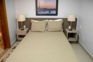 A bed or beds in a room at Onix Bueno Residence