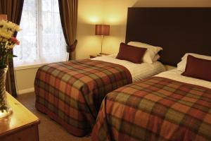 A bed or beds in a room at Macdonald Plas Talgarth Resort