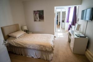 A bed or beds in a room at Holcombe Guest House