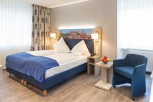 A bed or beds in a room at Ringhotel Loew's Merkur