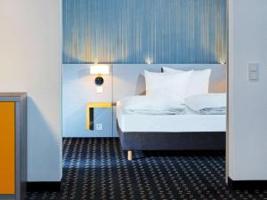 A bed or beds in a room at ibis Styles Stuttgart