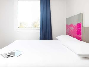 A bed or beds in a room at Ibis Styles Arles Palais des Congrès
