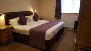 A bed or beds in a room at BEST WESTERN New Holmwood Hotel