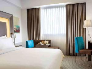 A bed or beds in a room at Novotel Bangka Hotel & Convention Center
