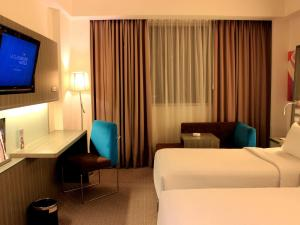 A television and/or entertainment center at Novotel Bangka Hotel & Convention Center