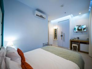 A bed or beds in a room at Bat Galim Boutique Hotel