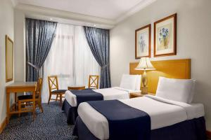A bed or beds in a room at Al Qibla Hotel