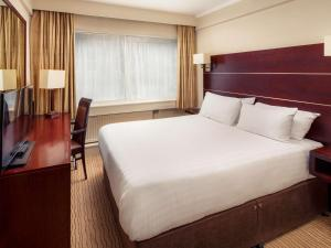 A bed or beds in a room at Mercure Glasgow City Hotel