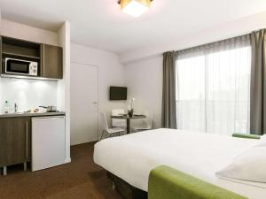 A bed or beds in a room at Aparthotel Adagio Access Nantes Viarme