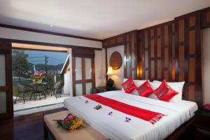 A bed or beds in a room at Baan Yin Dee Boutique Resort Phuket - SHA Plus