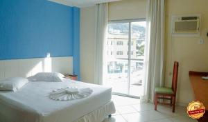 A bed or beds in a room at Acrópolis Marina Hotel