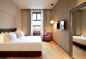 A bed or beds in a room at NH Collection Torino Piazza Carlina