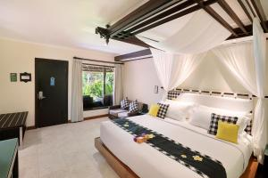 A bed or beds in a room at Legian Beach Hotel