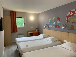 A bed or beds in a room at initial by balladins Tours Sud