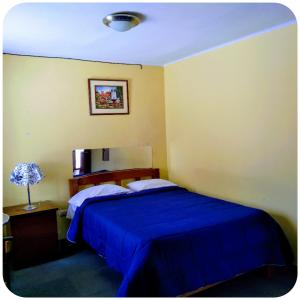 A bed or beds in a room at Casa Blanca Hospedaje