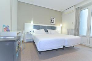 A bed or beds in a room at Hostal Alemana