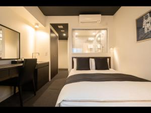 A bed or beds in a room at Roppongi Hotel S