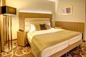 A bed or beds in a room at NordWest-Hotel Bad Zwischenahn