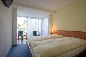 Ein Bett oder Betten in einem Zimmer der Unterkunft Hotel Klausenhof Flüeli