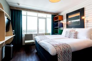 A bed or beds in a room at Strandhotel Westduin