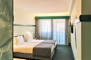 A bed or beds in a room at Amazonia Lisboa Hotel