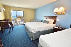 A bed or beds in a room at Coastal Palms Inn and Suites
