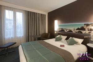 A bed or beds in a room at Mercure Pont d'Avignon Centre