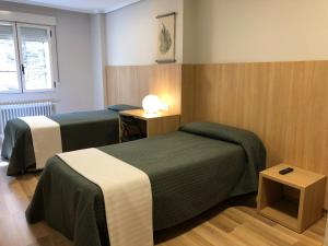 A bed or beds in a room at Hostal Bearan