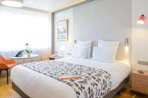 A bed or beds in a room at Mercure Marseille Centre Prado Vélodrome