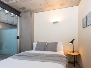 A bed or beds in a room at Luxury East Melbourne Apartment
