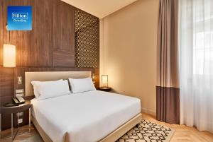 A bed or beds in a room at DoubleTree By Hilton Trieste