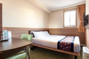 A bed or beds in a room at Dotonbori Hotel