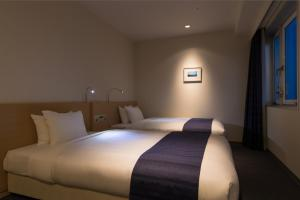 A bed or beds in a room at JR Kyushu Hotel Miyazaki