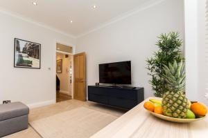 A television and/or entertainment center at Caledonian Bright One-Bedroom Apartment with Private Decked Garden